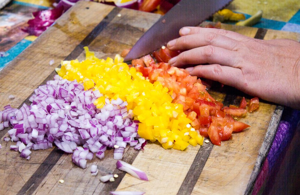 Chopped onions and peppers on cutting board