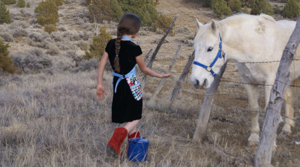 girl in red boots with white horse