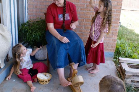mom spinning wool with little girls
