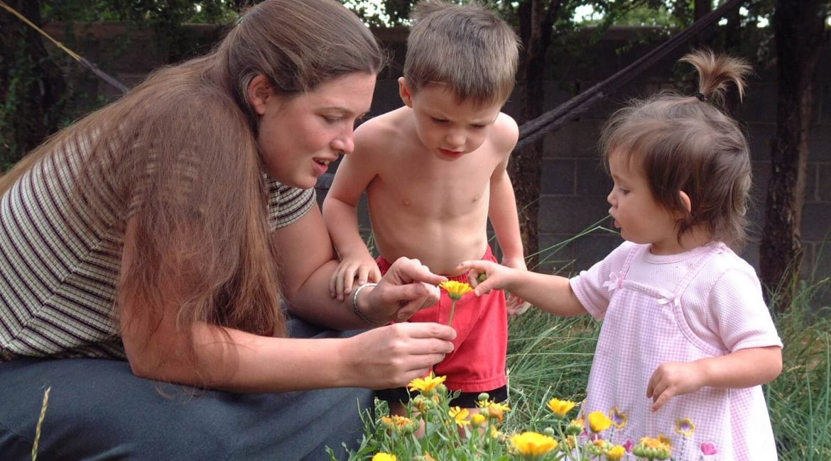 mom and kids looking at flower